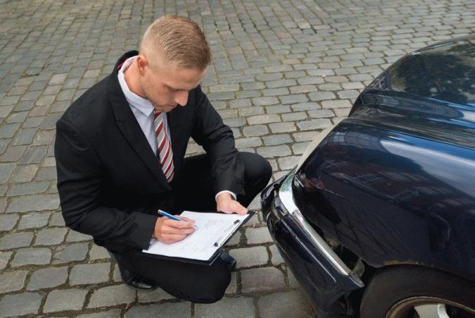специалист оценивает автомобиль