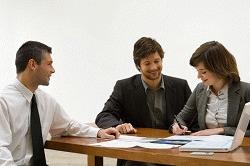 Young woman filling a document with a mid adult man and a real estate agent sitting with her
